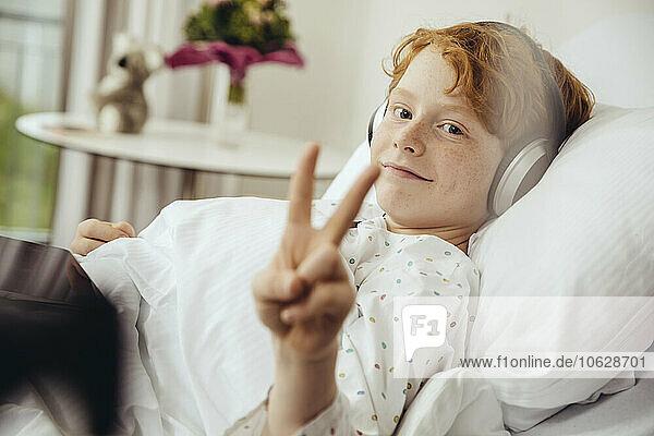 Ein kranker Junge liegt im Krankenhaus und macht ein Siegeszeichen  trägt Kopfhörer.