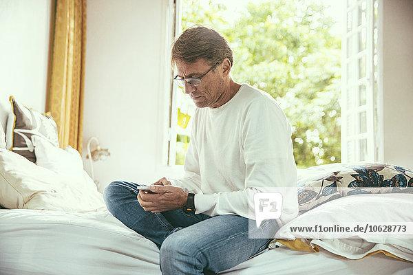 Mann sitzt auf dem Bett und schaut auf sein Smartphone.
