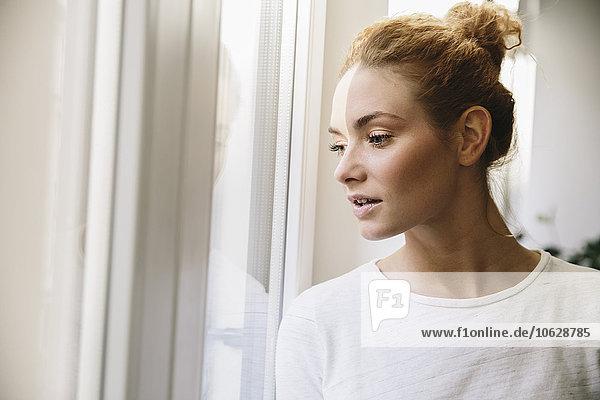 Junge Frau  die aus dem Fenster schaut und von der Sonne gestreichelt wird.