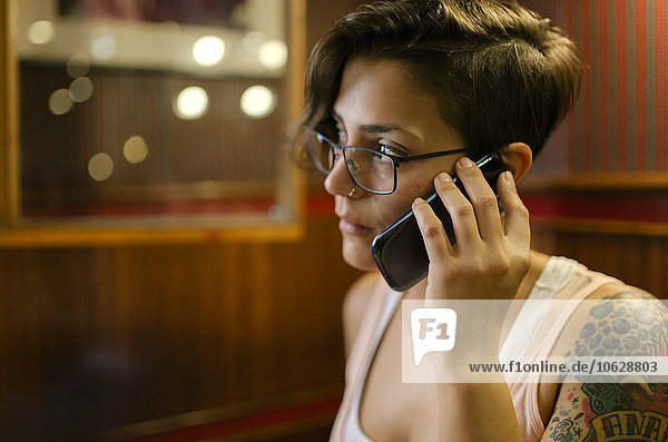 Tattooed young woman sitting in a coffee shop talking on phone