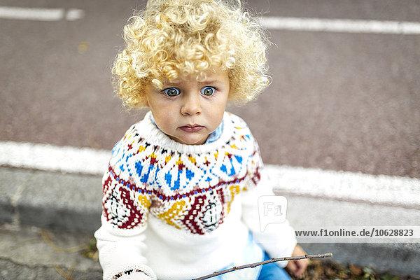 Porträt eines blonden kleinen Jungen mit gemustertem Strickpullover