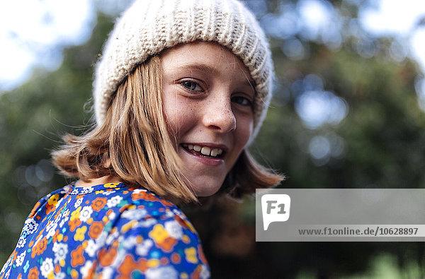 Portrait of smiling girl wearing woollen cap looking over her shoulder
