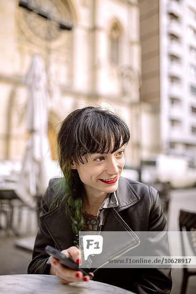 Spanien  Gijon  Junge Frau im Straßencafé mit Smartphone