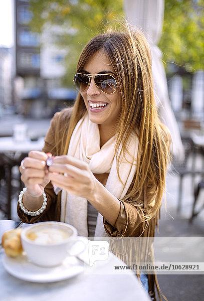 Spanien  Gijon  Junge Frau sitzend im Cafe mit Cappuccino