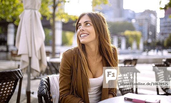 Spanien  Gijon  Junge Frau sitzend im Straßencafé