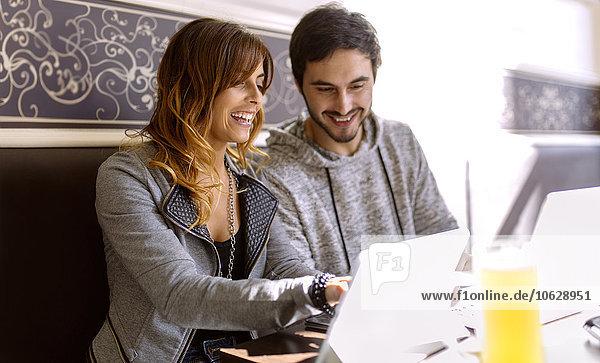 Lächelndes junges Paar mit digitalem Tablett in einer Kneipe