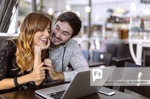 Glückliches junges Paar mit Laptop in einer Kneipe