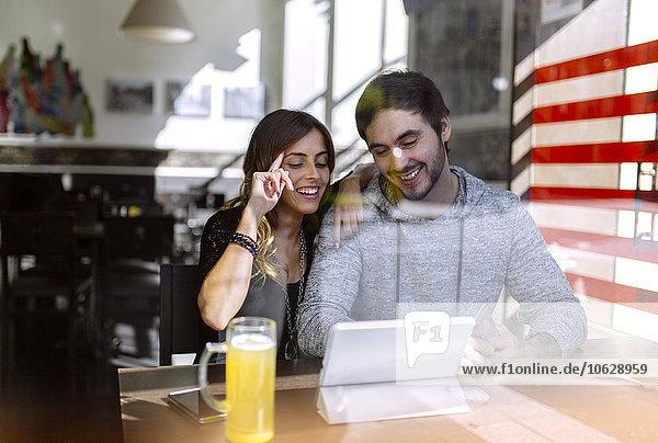 Glückliches junges Paar mit digitalem Tablett in einer Kneipe