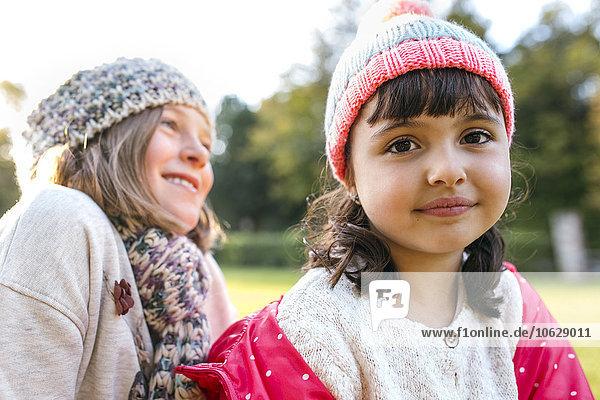 Two little girls wearing woolly hats