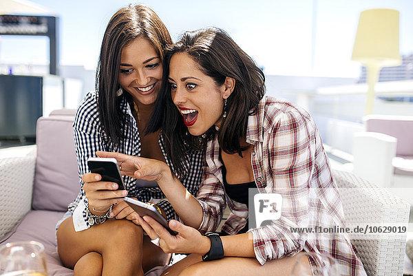 Zwei glückliche Freundinnen auf der Terrasse mit Blick aufs Handy