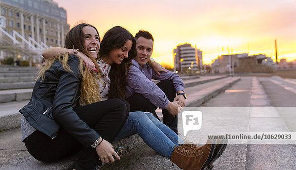 Drei Freunde  die sich bei Sonnenuntergang amüsieren