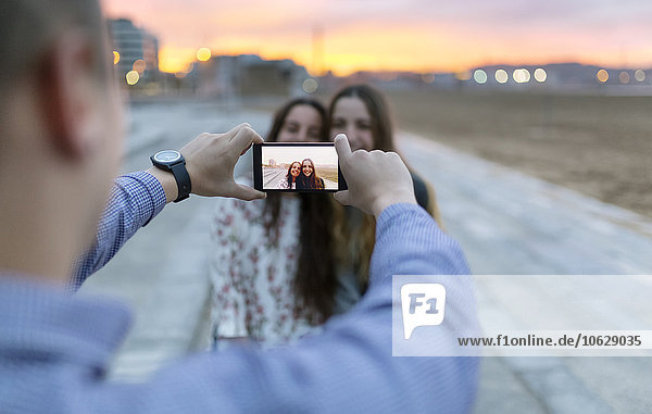 Mann  der in der Abenddämmerung einen Selfie von seinen Freunden nimmt