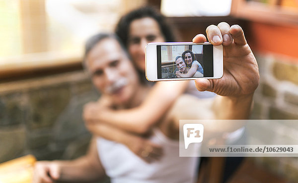 Photo of couple taking a selfie on display of smartphone