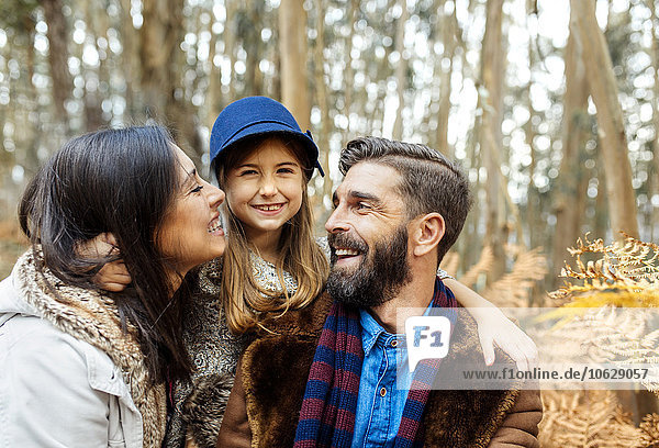 Glückliche Eltern mit kleiner Tochter in der Natur