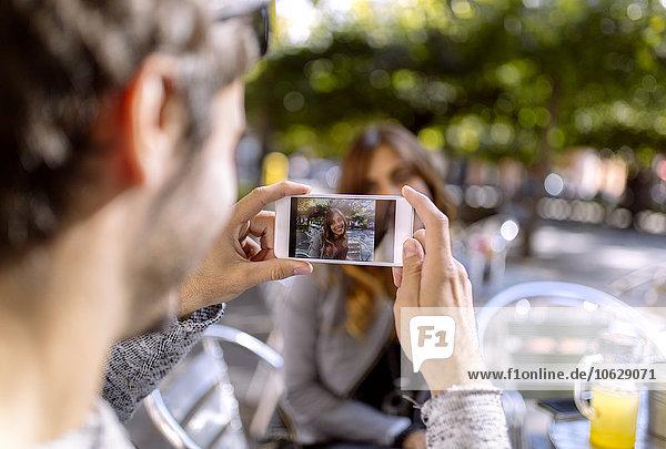 Junger Mann fotografiert seine Freundin mit Smartphone