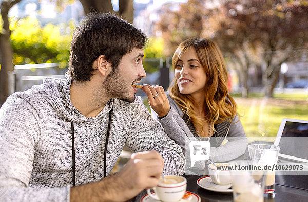 Junge Frau  die ihren Freund in einem Straßencafé füttert.