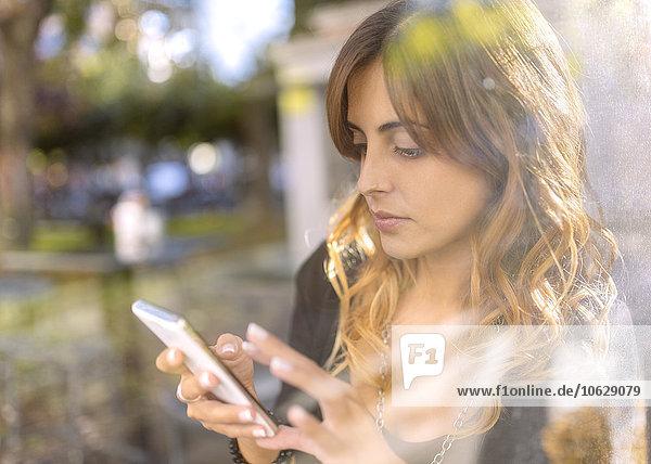 Nachdenkliche junge Frau schaut auf ihr Smartphone