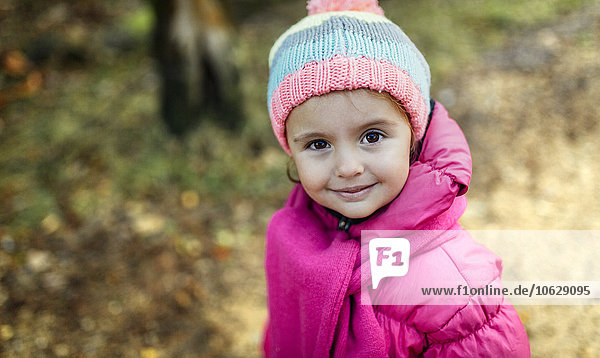 Portrait of smiling little girl wearing cap and scarf in autumn
