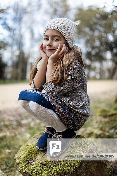 Portrait of smiling girl crouching on boulder