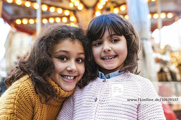 Zwei kleine Mädchen vor einem Karussell