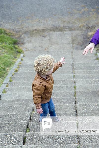 Kleines Mädchen  das die Treppe hinaufgeht und auf seine Mutter wartet.