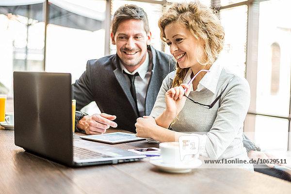 Zwei Geschäftspartner sitzen in einem Coffee-Shop und schauen auf den Laptop