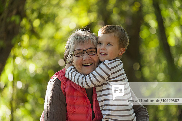 Smiling little boy embracing his happy grandmother