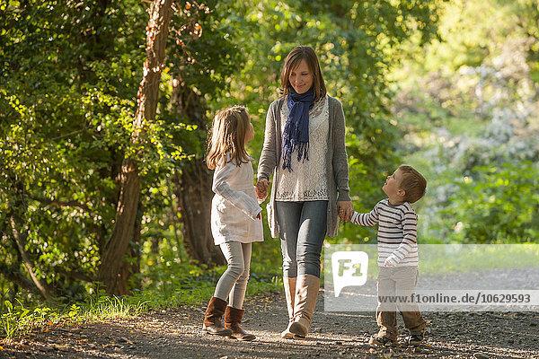 Mutter wandert mit ihren Kindern auf einem Waldweg