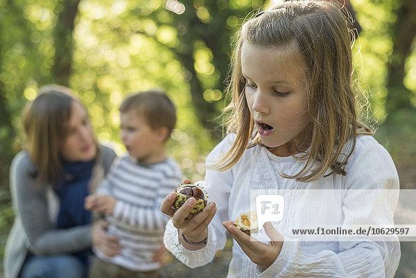 Erstauntes Mädchen schaut auf die Kastanie in der Hand