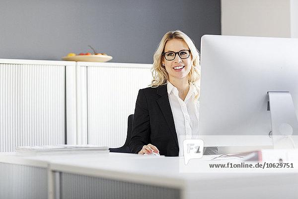 Lächelnde blonde Frau am Schreibtisch im Büro
