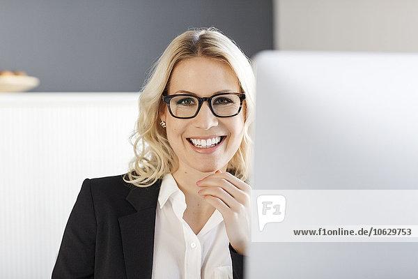Porträt einer lächelnden blonden Frau im Büro