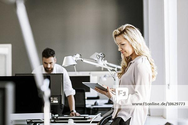 Zwei Kollegen im Büro mit digitalem Tablett und Computer