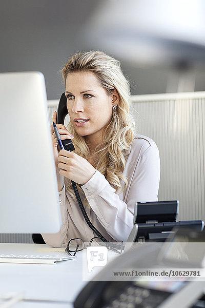 Blonde Frau im Büro am Telefon