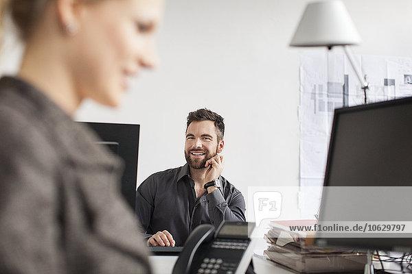 Mann im Büro sieht Frau an