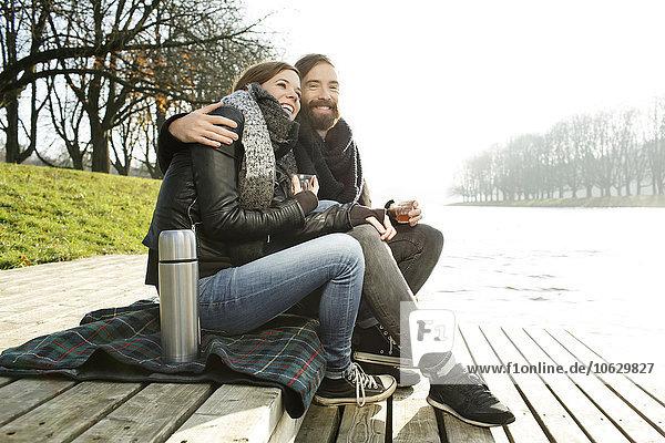 Glückliches Paar mit heißem Getränk am Flussufer im Herbst