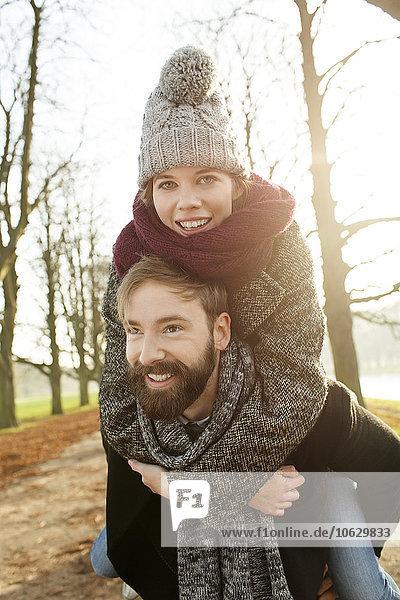 Junger Mann mit Freundin Huckepack im Herbst