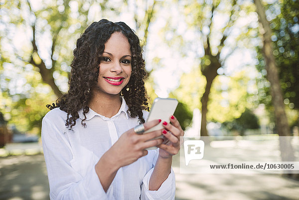 Portrait of smiling young woman with brown ringlets and red lips with smartphone