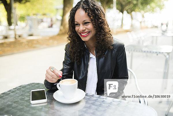 Porträt einer glücklichen jungen Frau mit einer Tasse Kaffee im Straßencafé