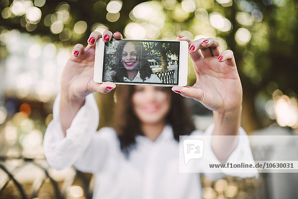 Young woman taking a selfie with her smartphone  close-up