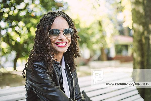 Porträt einer lächelnden Frau mit Sonnenbrille und Lederjacke  die auf einer Parkbank sitzt.