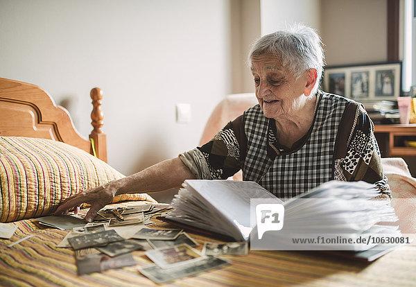 Seniorenfrau  die zu Hause alte Fotos in ein Fotoalbum einfügt.