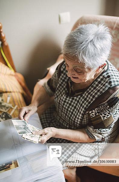 Seniorin beim Betrachten alter Fotos aus ihrer Kindheit