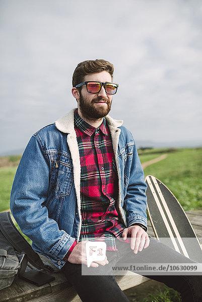 Junger lässiger Mann auf der Bank sitzend