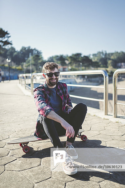 Spanien  La Coruna  Porträt eines lächelnden Hipsters mit Sonnenbrille auf dem Longboard