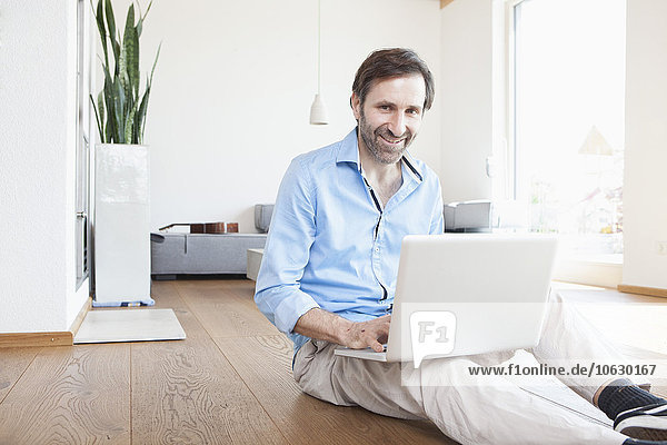 Erwachsener Mann zu Hause mit Laptop auf dem Boden sitzend