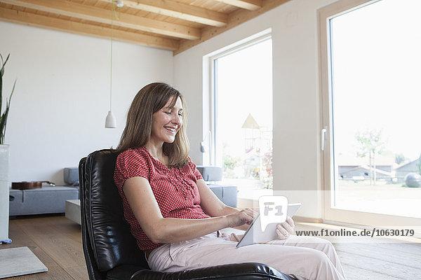 Reife Frau mit digitalem Tablett zu Hause