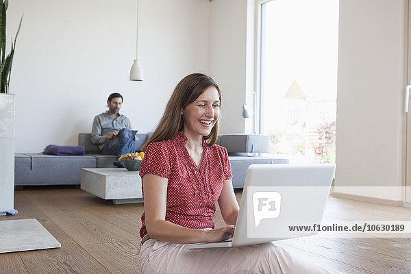 Reife Frau mit Laptop auf dem Boden im Wohnzimmer  Mann mit digitalem Tablett im Hintergrund