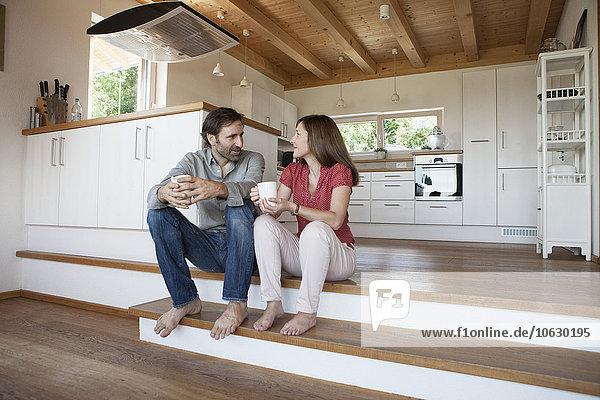Ein reifes Paar sitzt auf dem Boden und spricht über die Zukunft.