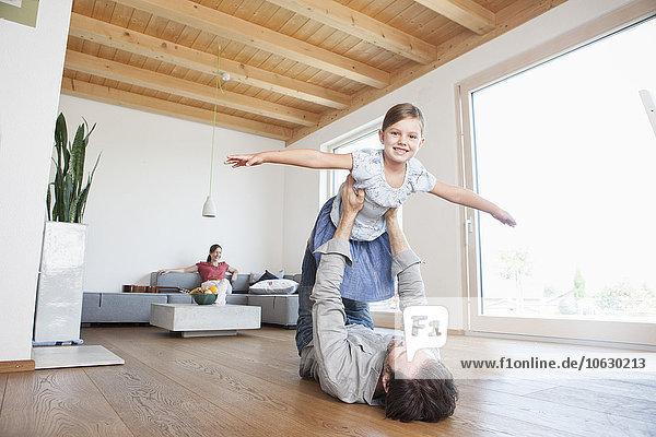Vater und Tochter spielen zu Hause und tun so  als ob sie fliegen würden.
