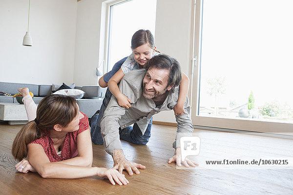 Glückliche Familie auf dem Boden liegend  mit Tochter spielend